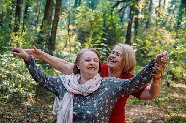 Zwei ältere frauen draußen im herbstpark genießen im leben, lachend. alte reife frauen lieben das aktive leben