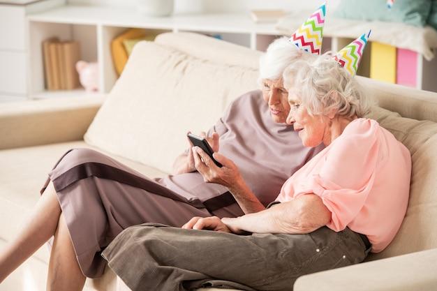Zwei ältere frauen in geburtstagskappen sitzen auf der couch, während sie neugierige dinge im smartphone besprechen