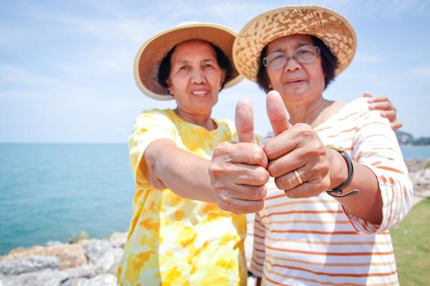 Zwei ältere frauen sind freunde, die im glücklichen ruhestand das meer besuchen.