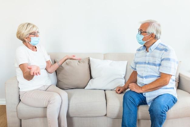 Zwei ältere freunde, die in sozialer entfernung sitzen und schutzmaske tragen