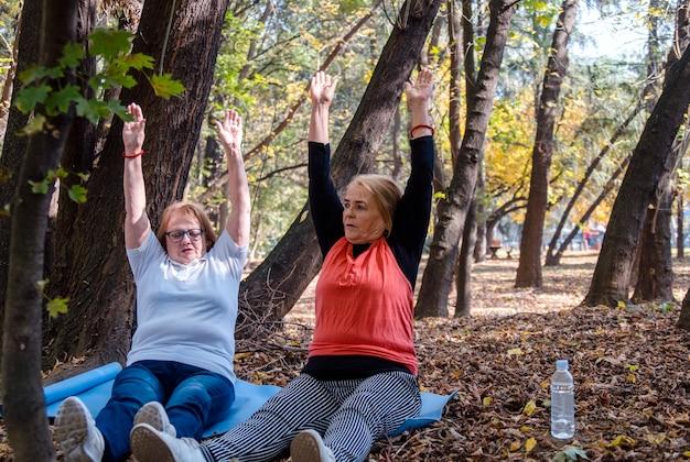 Zwei ältere freundinnen trainieren in der natur, sitzen auf der matte, praktizieren yoga. senioren, die sich im freien ausdehnen, um übergewicht zu verlieren. nie zu spät, um mit dem training zu beginnen