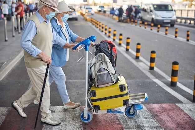 Zwei ältere kaukasische touristen, die die straße überqueren