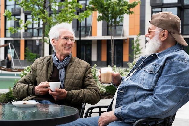 Zwei ältere männer in der stadt, die zusammen kaffee trinken und sich unterhalten