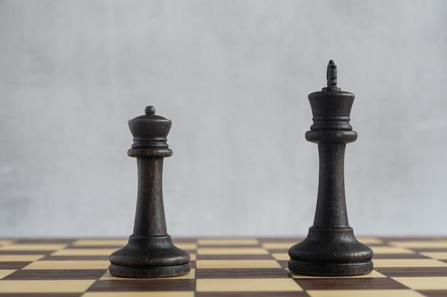 Zwei ältere schachfiguren schwarzer könig und schwarze dame