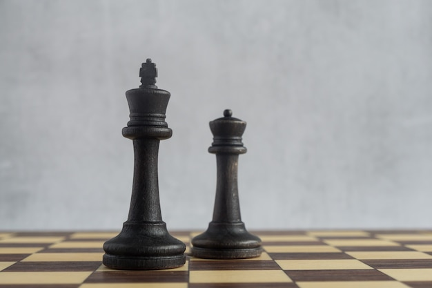 Zwei ältere schwarze schachfiguren auf dem brett