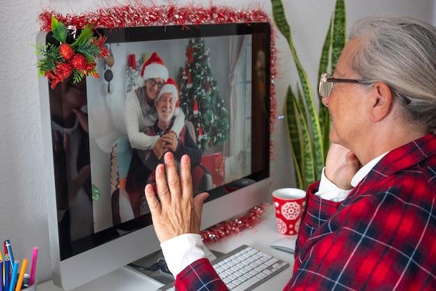 Zwei ältere schwestern per videoanruf für weihnachtsgrüße. eine frau sitzt mit ihrem mann und die andere allein