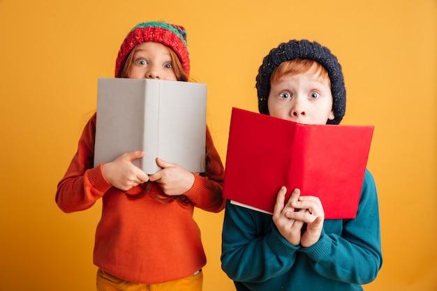Zwei ängstliche kleine rothaarige kinder, die gesichter mit büchern bedecken.