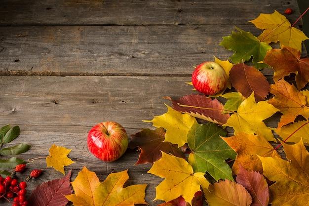 Zwei äpfel und herbstlaub auf hölzernem hintergrund