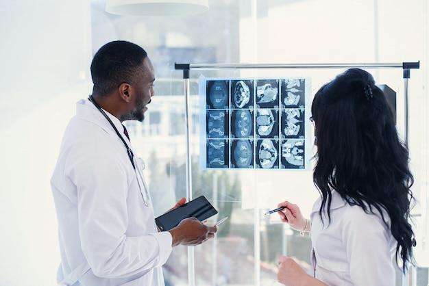 Zwei ärzte betrachten röntgenbilder. medizinisch. rückansicht des afroamerikanischen chefarztes und der kaukasischen frau, die eine röntgen-mrt bei klarem licht betrachten