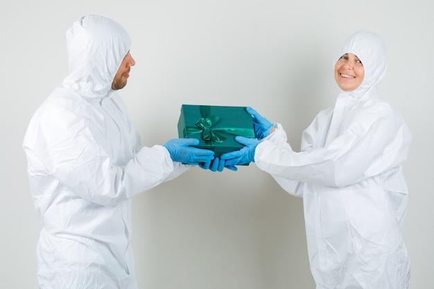 Zwei ärzte geben sich gegenseitig eine geschenkbox im schutzanzug