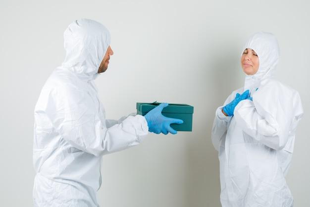 Zwei ärzte im schutzanzug, handschuhe, die sich gegenseitig die geschenkbox geben und hübsch aussehen.