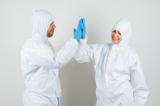 Zwei ärzte im schutzanzug, handschuhe klatschen in die hände und sehen glücklich aus