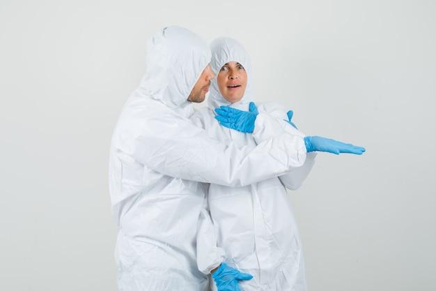Zwei ärzte in schutzanzügen, handschuhe, die etwas unerwartetes betrachten