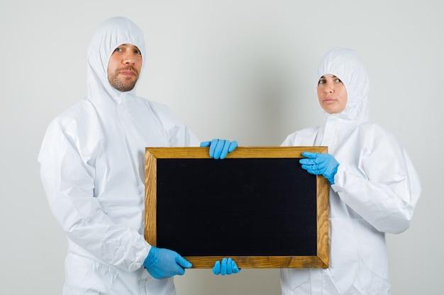 Zwei ärzte in schutzanzügen, handschuhe halten tafel und sehen selbstbewusst aus