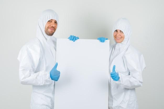 Zwei ärzte in schutzanzügen, handschuhe mit leerer leinwand