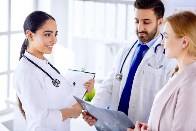 Zwei ärzte kommunizieren mit dem patienten und melden die diagnose dem patienten im krankenhaus.