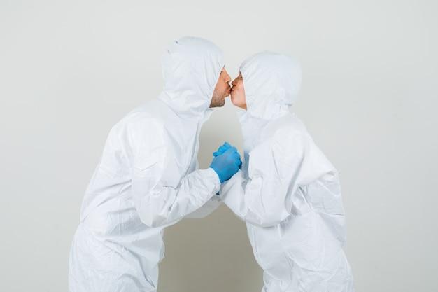 Zwei ärzte küssen sich, während sie sich in schutzanzügen an den händen halten