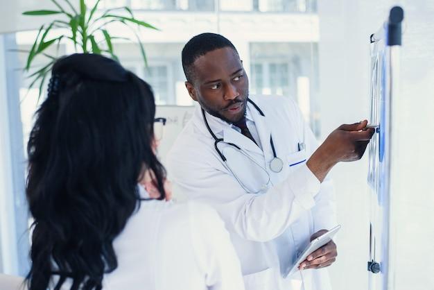 Zwei ärzte schauen sich eine röntgenaufnahme an und diskutieren das problem. medizintechniker, die auf die mrt-röntgenaufnahme des patienten zeigen. radiologe überprüft röntgen. medizinisches und radiologisches konzept.