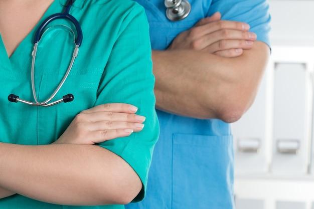 Zwei ärzte stehen mit verschränkten armen auf der brust und sind bereit zu arbeiten. gesundheitswesen und medizinisches konzept.