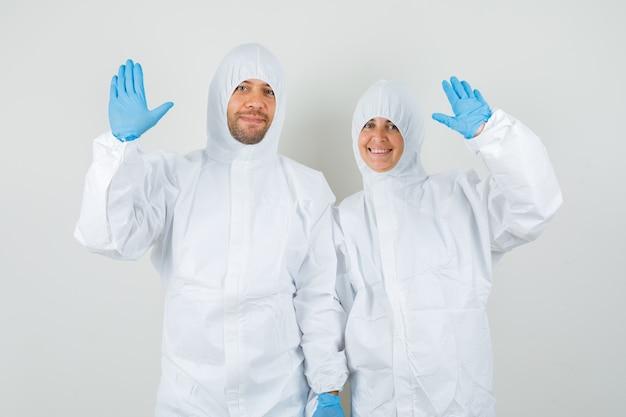 Zwei ärzte winken mit den händen, um in schutzanzügen hallo oder auf wiedersehen zu sagen