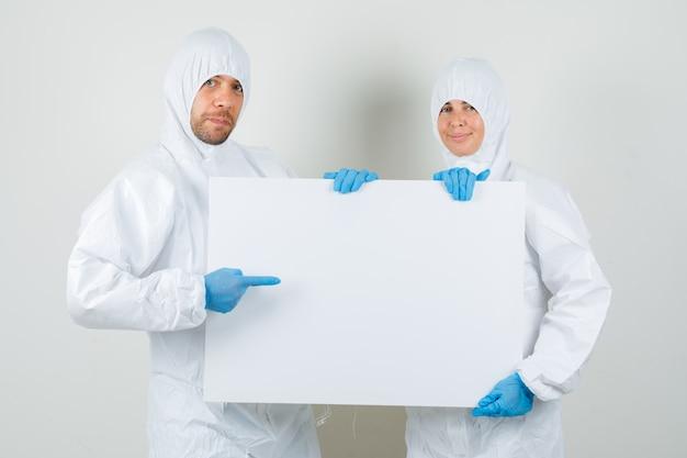 Zwei ärzte zeigen in schutzanzügen auf leere leinwand