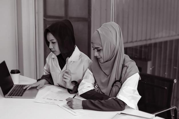 Zwei ärztinnen, die einen laptop verwenden, um sich über die behandlung des patienten zu beraten, mit ernsthaften emotionen, viel zeit, arbeit im krankenhaus, schwarz-weiß-ton und verschwommenem licht