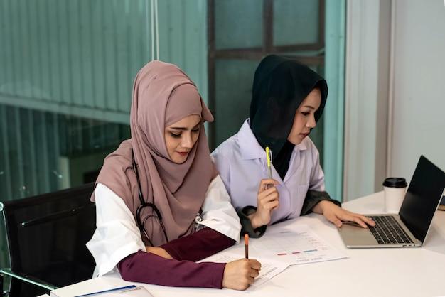 Zwei ärztinnen, die einen laptop verwenden, um sich über die behandlung des patienten zu beraten, mit ernsthaften emotionen, viel zeit und arbeit im krankenhaus