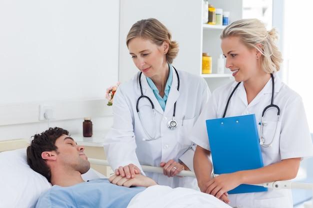 Zwei ärztinnen, die um einen patienten sich kümmern, der in seinem bett schläft