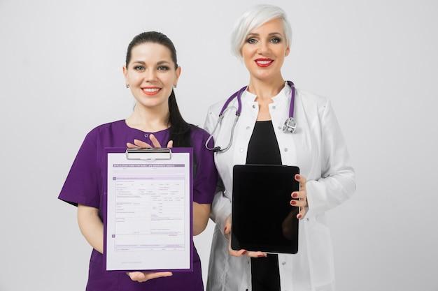 Zwei ärztinnen mit tablette und blatt mit analyse in den händen lokalisiert