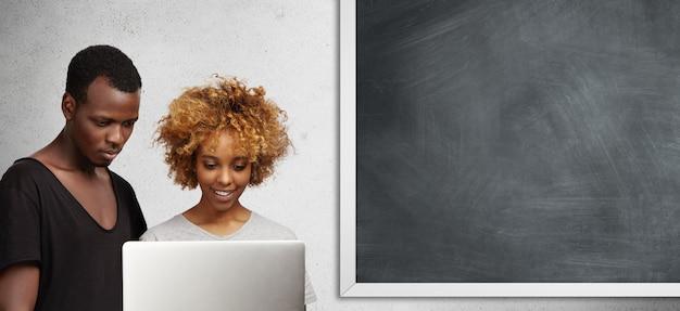 Zwei afrikanische college-studenten, die laptop im klassenzimmer verwenden.