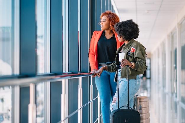 Zwei afrikanische mädchen mit koffern am flughafen das konzept von reisen und urlaub