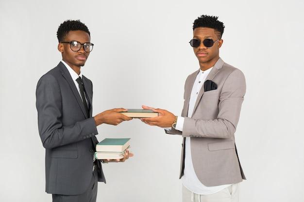 Zwei afrikanische männer in anzügen mit büchern