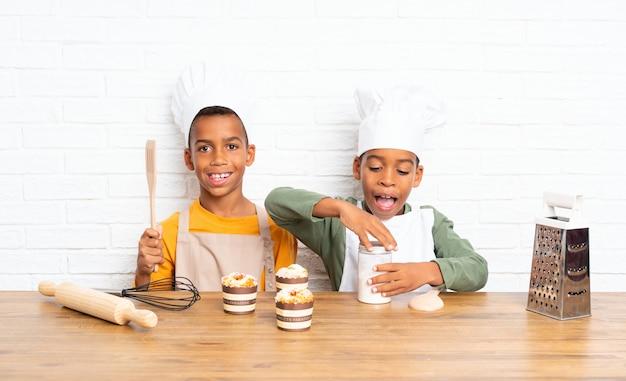 Zwei afroamerikaner-bruderkinder gekleidet als chef