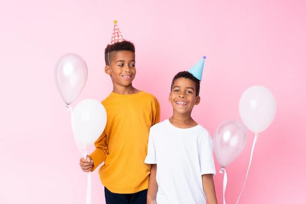 Zwei afroamerikanerbrüder, die ballon halten