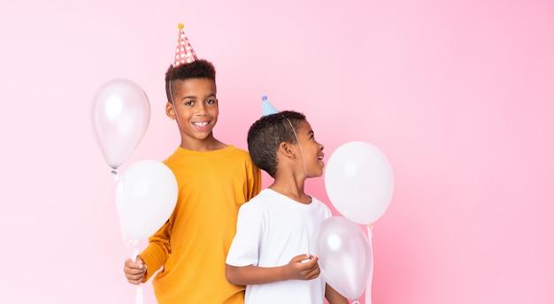 Zwei afroamerikanerbrüder, die ballone über lokalisiertem rosa halten