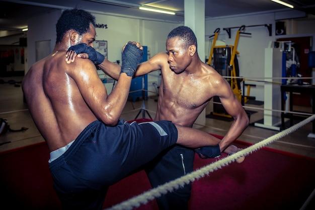 Zwei afroamerikanische kämpfer, die mma-takedown-techniken im ring üben