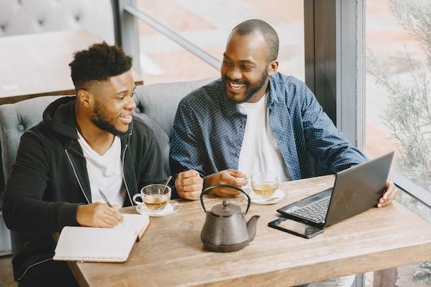 Zwei afroamerikanische männer, die hinter einem laptop arbeiten und in ein notizbuch schreiben. männer mit bart sitzen in einem café.