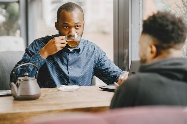 Zwei afroamerikanische männer unterhalten sich bei einer tasse tee. freund sitzt in einem café.