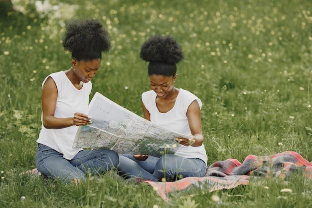 Zwei afroamerikanische schwestern, die in einer karte in einem park suchen