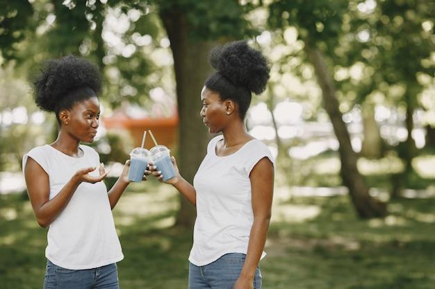 Zwei afroamerikanische schwestern erholen sich in einem park