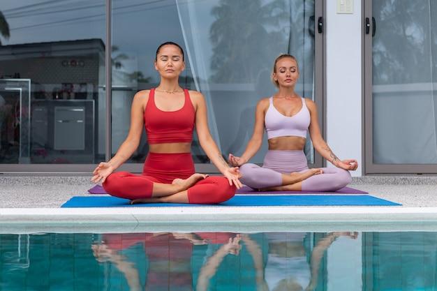 Zwei aktive asiatische und kaukasische frau, die yoga am pool der luxusvilla praktizieren