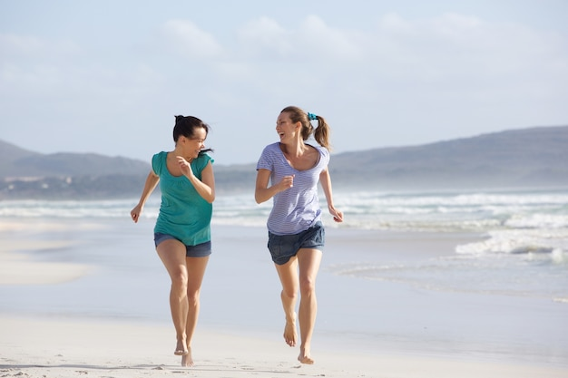 Zwei aktive frauen, die das leben am strand laufen lassen und genießen