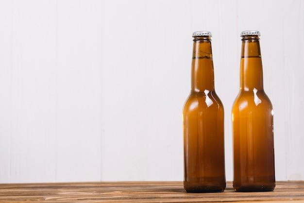 Zwei alkoholische flaschen auf hölzernen schreibtisch