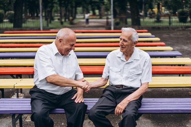 Zwei alte ältere erwachsene männer unterhalten sich draußen im stadtpark