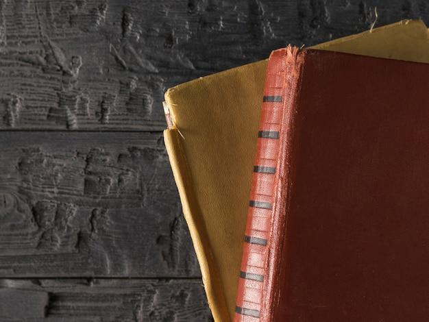 Zwei alte bücher auf einer schwarzen rustikalen tabelle. retro schreibpapier.