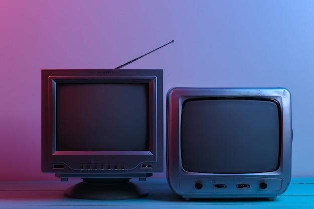 Zwei alte fernsehempfänger im roten blauen neonlicht. retro-welle, medien