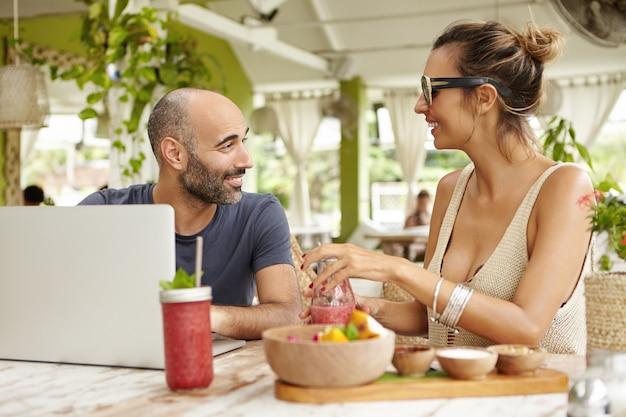 Zwei alte freunde unterhalten sich lebhaft, sitzen mit laptop und getränken am tisch und freuen sich, sich nach langer zeit wiederzusehen.