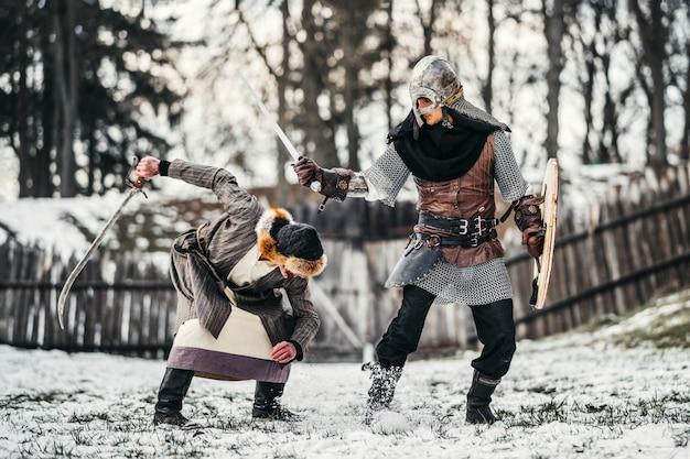 Zwei alte krieger in rüstung mit waffen, die mit schwertern im schnee kämpfen