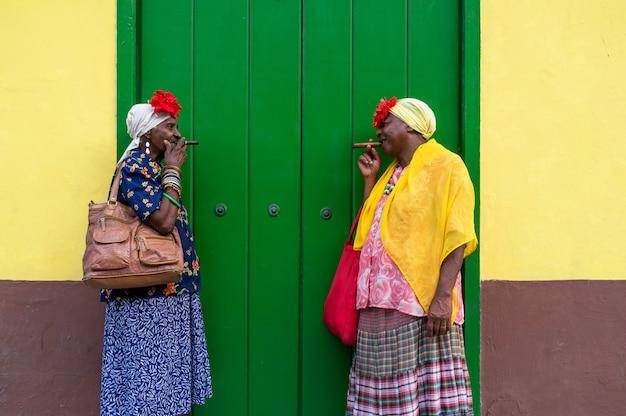 Zwei alte kubanische damen, die eine große zigarre rauchen