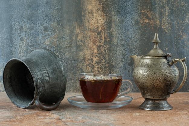 Zwei alte teekannen mit kräutertee auf marmorhintergrund